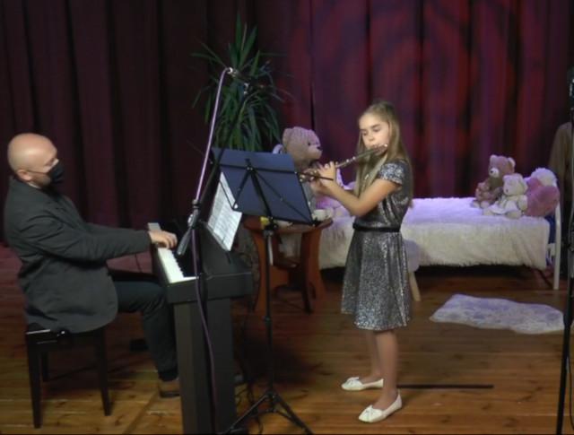 Dziewczynka gra na flecie, nauczyciel akompaniuje na fortepianie elektronicznym
