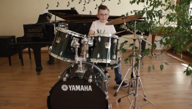 Chłopiec w białej koszulce gra na zestawie perkusyjnym