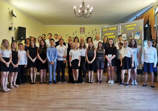 Nauczyciele i uczniowie na grupowej fotografii w sali koncertowej
